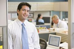 Businessman standing in cubicle smiling - stock photo