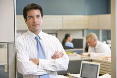 Businessman standing in cubicle - stock photo