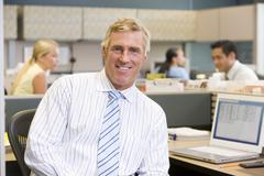 Businessman in cubicle smiling - stock photo