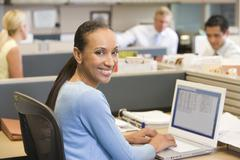 Businesswoman in cubicle using laptop smiling - stock photo