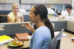 Businesswoman in cubicle eating salad and smiling Stock Photos