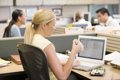 Businesswoman in cubicle using laptop eating sushi Stock Photos