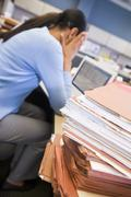 Businesswoman in cubicle with laptop and stacks of files Stock Photos