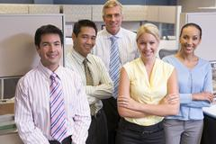 Business team standing in cubicle smiling - stock photo