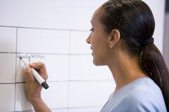 Businesswoman indoors writing on erasable board - stock photo