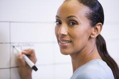Businesswoman indoors writing on erasable board smiling Stock Photos