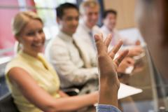 Five businesspeople at boardroom table with focus on businessman's hand - stock photo