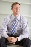 Businessman sitting indoors smiling - stock photo