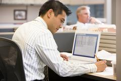 Businessman in cubicle with laptop writing - stock photo
