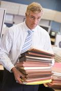 Businessman standing in cubicle with stacks of files Stock Photos