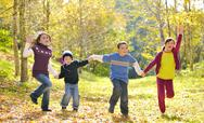 Happy kids and autumn leaves Stock Photos