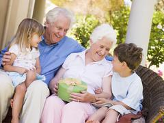 Grandparents with grandchildren on patio with gift smiling - stock photo
