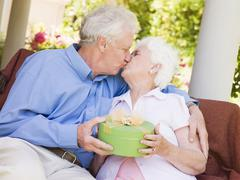 Husband giving wife gift on patio and kissing her - stock photo