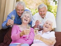 Two couples on patio drinking champagne and smiling - stock photo