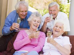 Two couples on patio drinking champagne and smiling Stock Photos