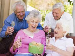 Two couples on patio with champagne and gift smiling Stock Photos