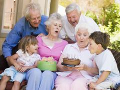 Grandparents and grandchildren on patio with cake and gift smiling Stock Photos