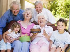 Grandparents and grandchildren on patio with cake and gift smiling - stock photo