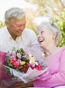 Husband giving wife flowers outdoors smiling Stock Photos
