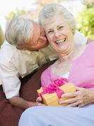 Husband giving wife gift on patio kissing her and smiling - stock photo