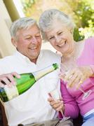 Stock Photo of Couple on patio drinking champagne and smiling