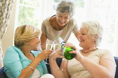 Three women in living room drinking champagne and smiling Stock Photos