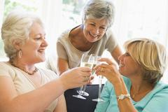Three women in living room toasting champagne and smiling Stock Photos