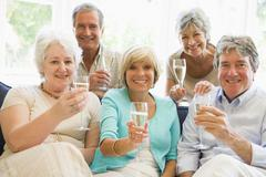 Five friends in living room drinking champagne and smiling Stock Photos
