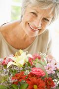 Woman with flowers smiling Stock Photos