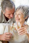 Couple in living room toasting champagne and smiling Stock Photos