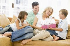 Family in living room with mother receiving gift and smiling Stock Photos