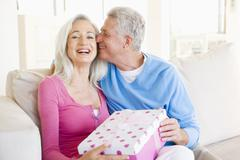 Husband giving wife gift in living room kissing her and smiling - stock photo