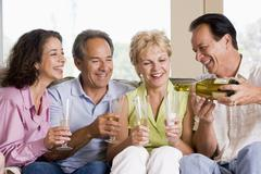 Two couples in living room drinking champagne and smiling - stock photo