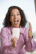 Woman with winning lottery ticket excited and smiling - stock photo