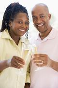 Couple toasting champagne and smiling - stock photo