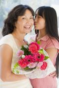 Granddaughter kissing grandmother on cheek holding flowers and smiling - stock photo