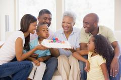 Family in living room smiling with young boy blowing out candles on cake - stock photo
