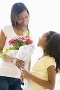 Mother giving daughter flowers and smiling Stock Photos