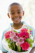 Young boy holding flowers smiling - stock photo