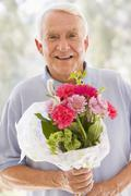 Man holding flowers and smiling - stock photo