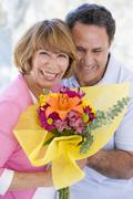 Stock Photo of Husband and wife holding flowers and smiling