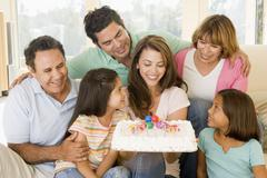 Family in living room with cake smiling Stock Photos