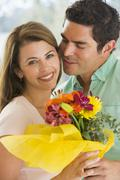 Husband and wife holding flowers and smiling Stock Photos
