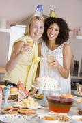 Two women at party holding drinks standing by food table smiling - stock photo