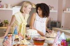 Two women at party getting sandwiches smiling Stock Photos