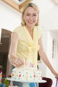 Woman putting candles in cake smiling - stock photo