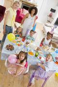 Young children at party with mothers sitting at table with food smiling - stock photo