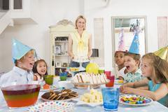 Young children at party sitting at table with mother carrying cake and smiling Stock Photos