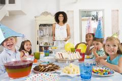 Young children at party sitting at table with mother carrying cake and smiling - stock photo