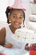 Young girl wearing party hat with cake in front of her smiling - stock photo